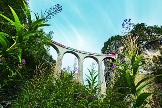 Schweiz. ganz natuerlich. Bernina Express: Chur-Tirano. Landwasserviadukt bei Filisur, 65m hoch und 136m lang. Wahrzeichen der RhB und UNESCO-Weltkulturerbe.